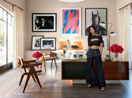 Kourtney in her home office, which is furnished with a vintage Jules Leleu desk and Pierre Jeanneret chairs; the arrangement of art includes a vibrant work on paper by Bridget Riley.