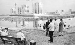 Onlookers by the lake watch the construction of Thamesmead, Greenwich, London