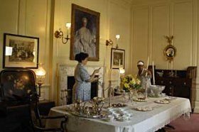 Preparing for a soirée in the ostentatiously Colonial Revival Carter's Grove dining room, Mistress Molly McCrea, interpreted by Sandy Holsten, directs maid Edmonia Washington, portrayed by Jean Mitchell.