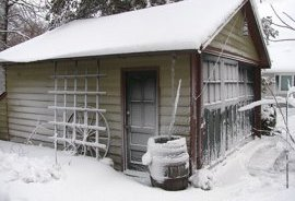snow covered garage rain barrel