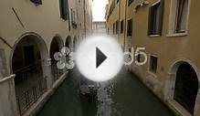 Paddling A Gondola By A Building With Arches In Venice